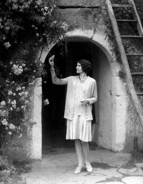 1920s-1930s Woman In Flapper Outfit Standing In Front Of Whitewashed Archway With Flowers Picking Bud Brittany France - Item # PPI177647LARGE
