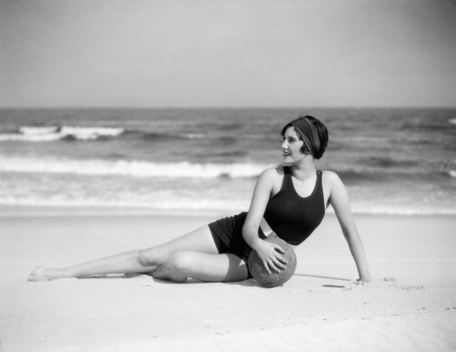 1920s Woman In Bathing Suit Stretched Out On Beach In Front Of Water Holding Ball Print By Vintage Collection - Item # PPI177147LARGE