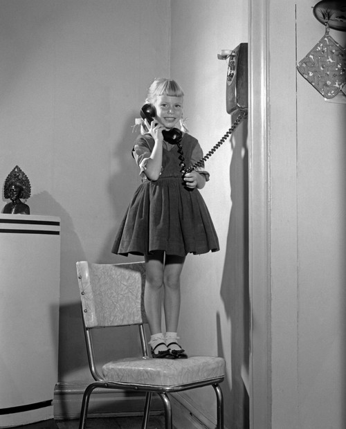 1960s-1950s Young Girl Standing On Kitchen Chair Looking At Camera Talking On Wall Telephone Print By Vintage Collection - Item # PPI179567LARGE