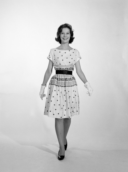 1960s-1950s Smiling Woman Walking To Looking At Camera Wearing Polka Dot Cotton Dress High Heel Shoes And White Gloves - Item # PPI179111LARGE