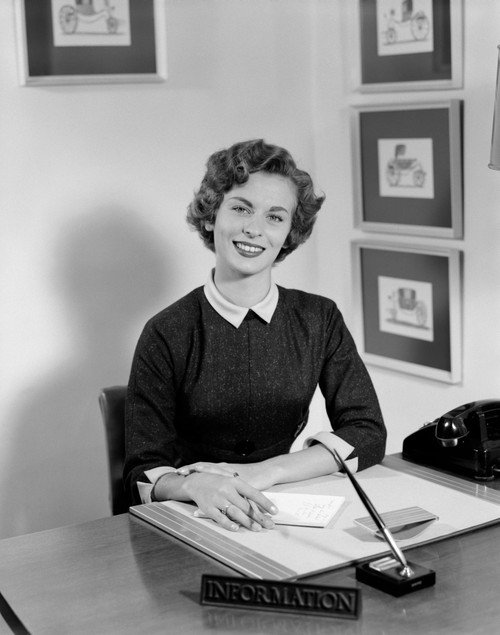 1950s Woman Sitting At Information Desk In Office Holding Pencil And Paper Poster Print By Vintage Collection (22 X 28) - Item # PPI177542LARGE