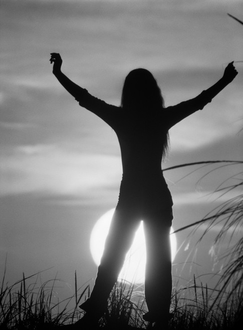 1970s Silhouetted Figure Woman Standing Arms Stretched Up Raised Above Head On Grassy Hill Against Setting Sun Print By - Item # PPI179412LARGE