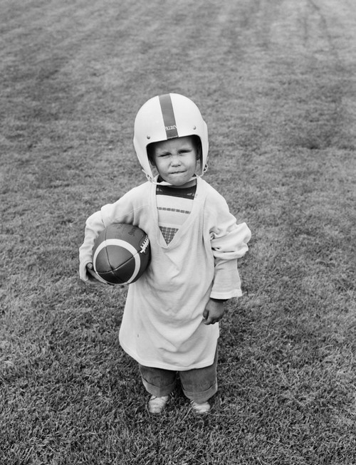 1950s Boy Standing In Grass Wearing Oversized Jersey And Helmet Holding Football Looking At Camera Print By Vintage - Item # PPI177020LARGE