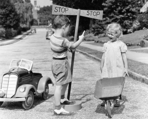 1930s-1940s Boy Playing Traffic Cop Pointing To Stop Sign Halting Girl With Wheelbarrow Print By Vintage Collection - Item # PPI177434LARGE