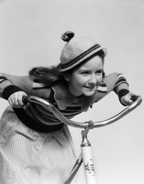 1930s Smiling Eager Little Girl In Knit Cap And Matching Sweater Riding Bike Leaning Into Handlebars Print By Vintage - Item # PPI177212LARGE