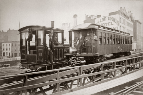 1880s Men On Board Elevated Locomotive & Passenger Car On East 42Nd Street Grand Union Hotel In Background New York City - Item # PPI195700LARGE