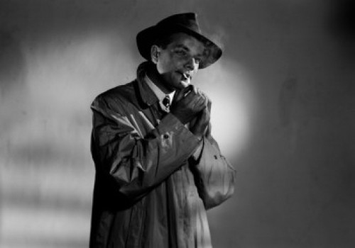 Portrait of young man wearing coat and hat and smoking cigarette  studio shot Poster Print - Item # VARSAL255419913