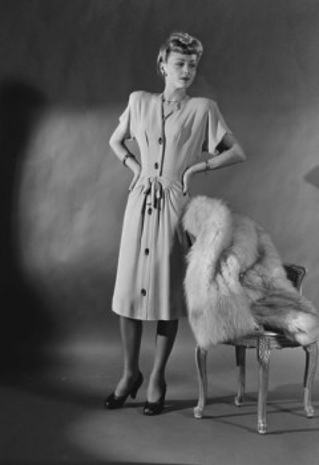 Portrait of elegant woman standing by chair covered with fur Poster Print - Item # VARSAL255419731