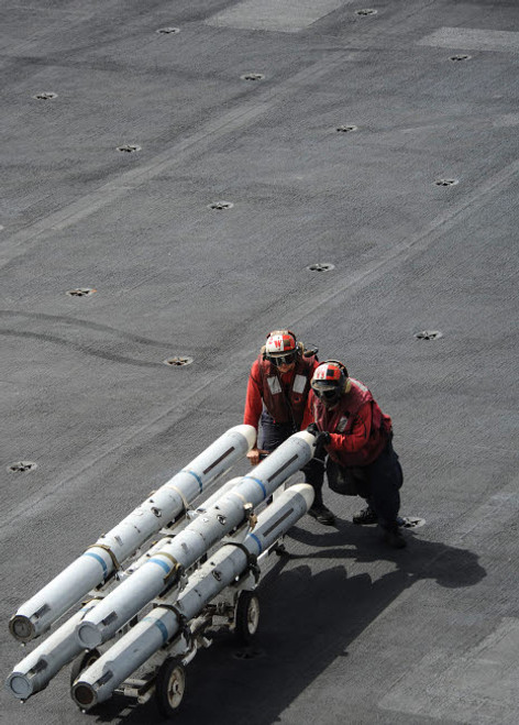 Ordnancemen push ordnance across the flight deck of USS Nimitz Poster Print by Stocktrek Images - Item # VARPSTSTK107803M