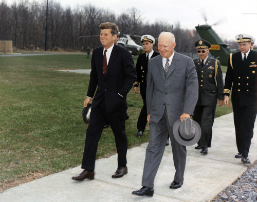 President Kennedy And Former President Eisenhower Walk Ahead Of Military Aides At Camp David. The Group Met To Discuss Foreign Relations With Cuba After The Disastrous Bay Of Pigs Invasion. April 22 History - Item # VAREVCHISL033EC896