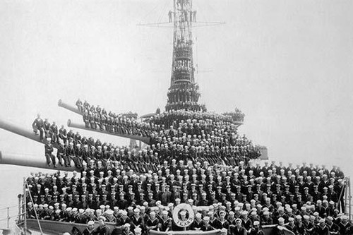 629 of the 1052 compliment of sailors pose on the deck of the USS Texas.  They sit on the massive 14 inch guns on this U.S. Navy battleship.  The Texas was commissioned in 1914 and fought in combat through World War II. Poster Print by unknown - Item