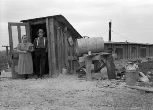 Dugout Home, 1939. /Na Farm Couple From Drought Stricken Oklahoma Standing In The Doorway Of Their Dugout Basement Home In Dead Ox Flat, Malheur County, Oregon. Photograph By Dorothea Lange, October 1939. Poster Print by Granger Collection - Item # V