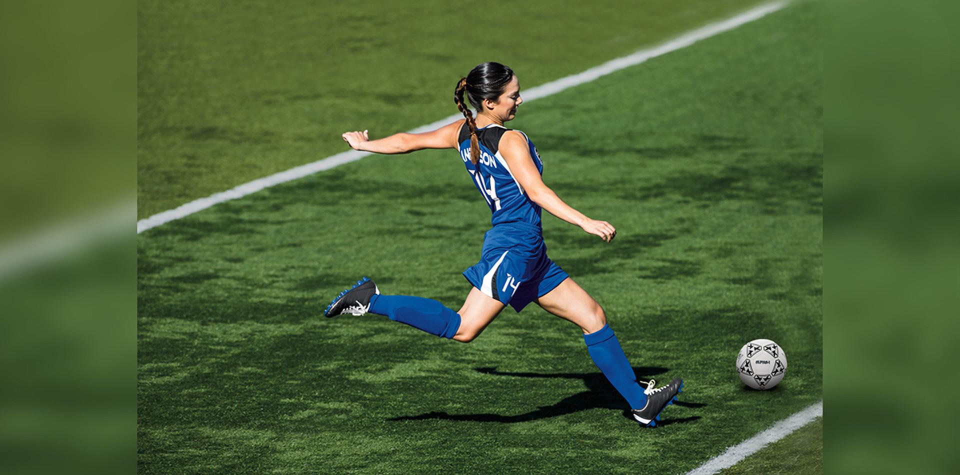 Girl kicking soccer ball on field