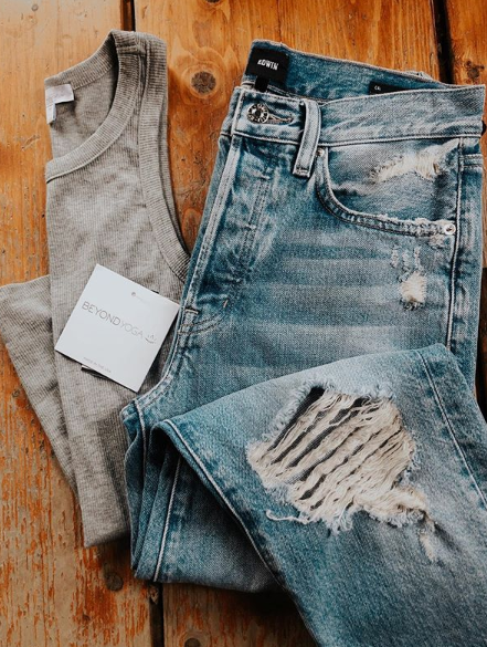 Women's distressed denim by Edwin Jeans and classic racerback tank by Beyond Yoga.