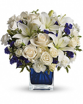 White roses, white asiatic lilies and white miniature carnations are mixed with bursts of purple statice and green pitta negra. Delivered in a glass Cube.