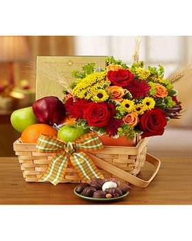 fresh apples, oranges and sweet chocolates (a perfect mix for sharing) along with a vibrant arrangement of red and orange roses, yellow poms and more