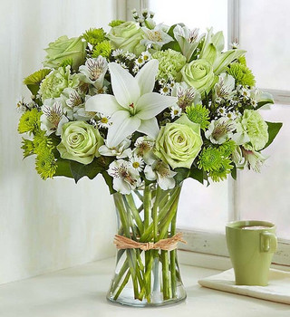 charming arrangement is hand-designed with the freshest blooms in delicate shades of green and white, arranged in a classic gathering vase tied with raffia.