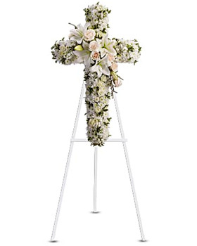 Beautiful flowers such as white roses, white spray roses, oriental lilies, stock, leptospermum, cushion and button spray chrysanthemums on an easel-mounted standing cross.