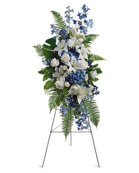 This standing spray presented on an easel includes fragrant white lilies and tropical greenery.This standing spray includes blue delphinium, white roses and asiatic lilies, plus tropical ferns and leaves