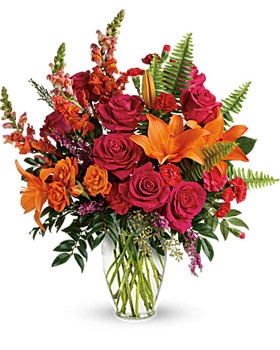 Hot pink roses, orange spray roses, orange asiatic lilies, hot pink carnations, red miniature carnations, orange snapdragons, and pink heather are accented with sword fern, seeded eucalyptus, and lemon leaf.