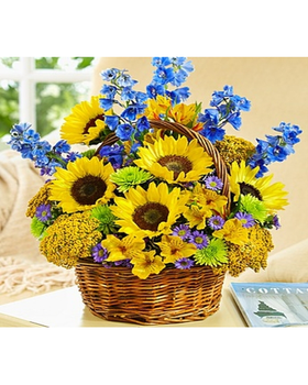 hand-designed bouquet of sunflowers, delphinium and more arrives in a rustic willow basket
