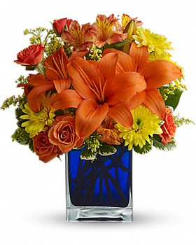 orange Asiatic lilies, orange alstroemeria, yellow cushion spray chrysanthemums, solidago and orange spray roses accented with assorted greenery