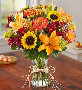 All-around arrangement with autumn-colored roses, sunflowers, orange Asiatic lilies, red and autumn-colored daisy poms; accented with wheat, solidago and assorted greenery