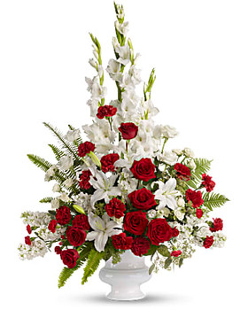 Red and white roses are arranged with white oriental lilies, white gladioli, white stock and red carnations in a white urn