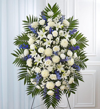"""Standing spray arrangement with white roses, Asiatic lilies, football mums, carnations and monte casino; blue delphinium; accented with soft, lush greenery.  measures approximately 56""""H x 38""""L without stand. Arrives on an easel.Appropriate for the funeral home or grave site"""