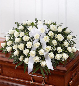 Half casket cover arrangement of white roses, monte casino and fresh greenery; accented with a white satin ribbon