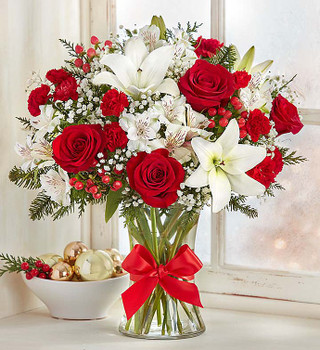 All-around arrangement with red roses, carnations, white Asiatic lilies and Peruvian lilies, accented with baby's breath, and assorted Christmas greenery