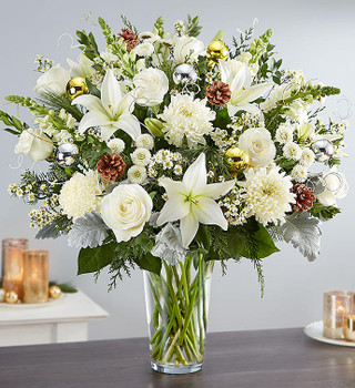 All-around arrangement with white roses, Asiatic lilies, football mums, snapdragons, button poms, waxflower and monte casino; accented with assorted Christmas greenery, pinecones; silver & gold glass ornaments, and shimmering accents
