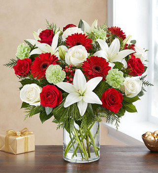All-around arrangement with red roses and Gerbera daisies; white roses and Asiatic lilies; lime green hydrangeas and carnations; accented with red hypericum berries and assorted Christmas greenery