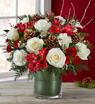 All-around arrangement with white roses, carnations; red Peruvian lilies, burgundy mini carnations; accented with assorted Christmas greenery, birch branches, and pine cones
