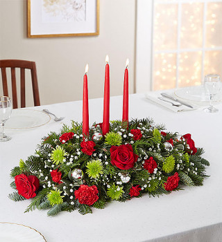 Centerpiece arrangement with red roses, carnations, and mini carnations; green Athos poms; accented with baby's breath, assorted Christmas greenery, silver decorative balls, and candles