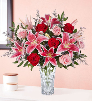 All-around arrangement with long-stem red roses, pink roses and Stargazer lilies, purple limonium; accented with assorted greenery