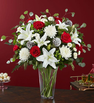All-around arrangement with red roses; white Oriental lilies, football mums and button poms; accented with green hypericum berries, assorted Christmas greenery and glittery, snowy pinecones