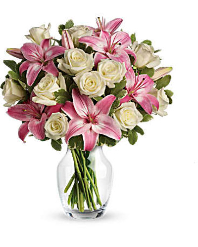 One dozen white roses are mixed with pink asiatic lilies and variegated pittosporum in a classic clear glass rose vase.