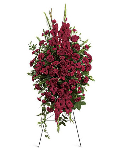 The radiant arrangement includes red roses, red gladioli, red carnations and red miniature carnations, accented with assorted greenery.