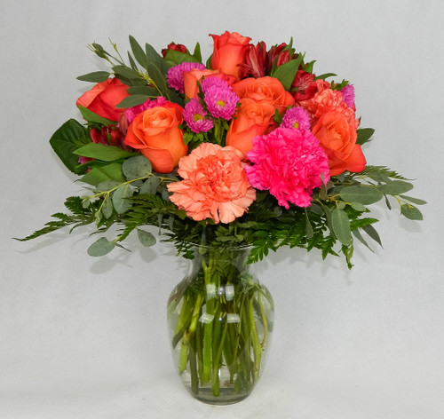 Lush orange roses, hot pink matsumoto asters and hot pink carnations are accented with bright greenery in a clear glass vase.