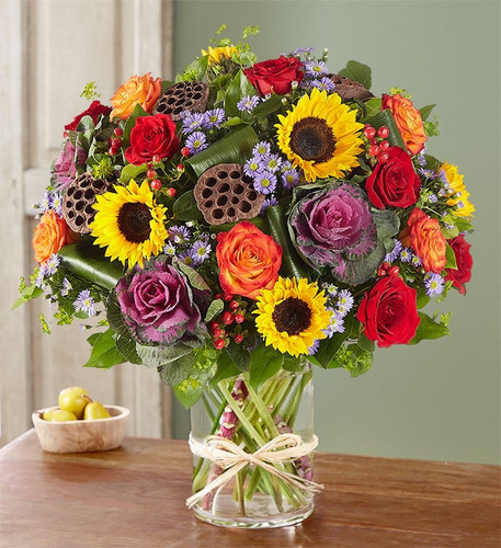 """We've taken one of our most impressive bouquets and filled it with lots of rich color and texture for Fall. Vibrant red and bi-color roses, brilliant sunflowers and cheery purple monte casino are gathered with unique accents in a chic glass cylinder vase to turn any birthday, anniversary or Autumn day into a """"grand"""" celebration"""