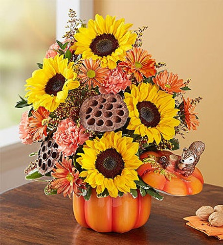 One-sided arrangement with sunflowers, orange carnations and fall-colored daisy poms; accented with red tinted solidago, dried lotus pods and assorted greenery