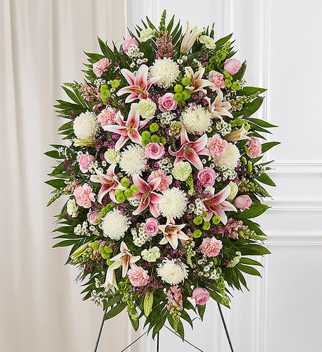"Standing spray arrangement with pink roses, Oriental lilies, snapdragons and carnations; white mums and monte casino; lime green carnations; green button poms; purple waxflower; Bells of Ireland; accented with soft, lush greenery. Measures approximately 56""H x 38""L without stand,Arrives on an easel,Appropriate for the funeral home or grave site"