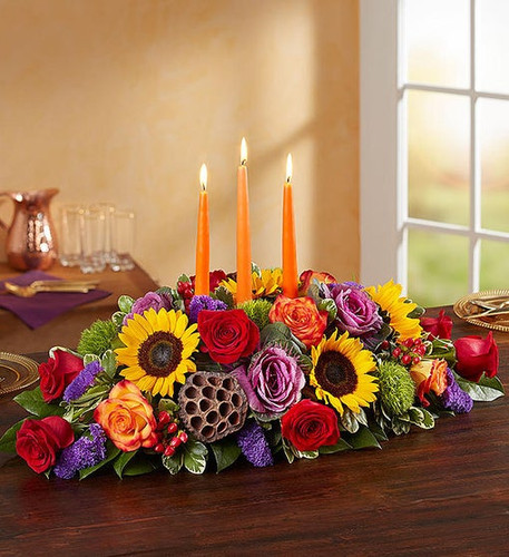 All-around centerpiece arrangement with red and autumn-colored roses; sunflowers, red hypericum, purple statice and kale; accented with assorted greenery and dried lotus pods