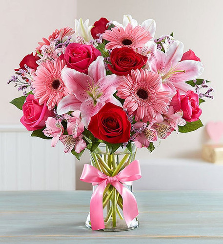 All-around arrangement with red and hot pink roses, pink Stargazer lilies, Gerbera daisies, Peruvian lilies (alstroemeria) and limonium; accented with assorted greenery, artistically designed in a clear glass vase accented with a pink satin ribbon