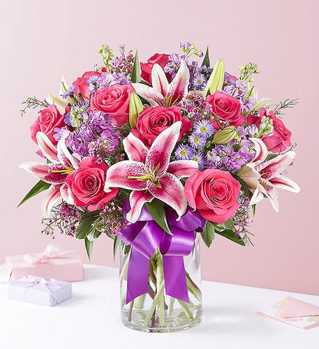 All-around arrangement with hot pink roses, pink Stargazer lilies, lavender stock, purple waxflower and monte casino; accented with assorted greenery Artistically designed in a clear glass cylinder vase accented with a purple satin ribbon