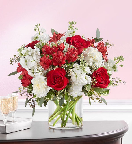 All-around arrangement with red roses and Peruvian lilies (alstroemeria); white carnations, stock and waxflower; accented with assorted greenery Artistically designed a clear glass cylinder vase