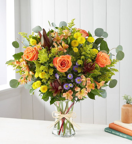 All-around arrangement with orange roses and Peruvian lilies (alstroemeria), red Leucadendron, yellow button poms and purple monte casino; accented with silver dollar eucalyptus and assorted greenery
