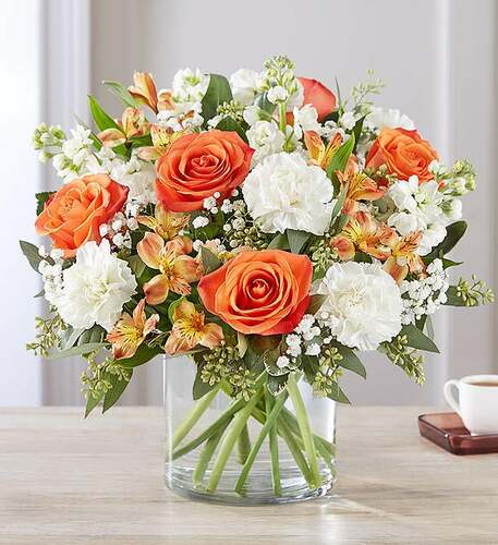 All-around arrangement with orange roses and Peruvian lilies (alstroemeria), white carnations and stock; accented with baby's breath and assorted greenery