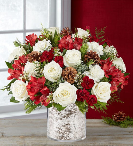 All-around arrangement with white roses and carnations; red Peruvian lilies (alstroemeria);  mini carnations; accented with assorted Christmas greenery and pinecones
